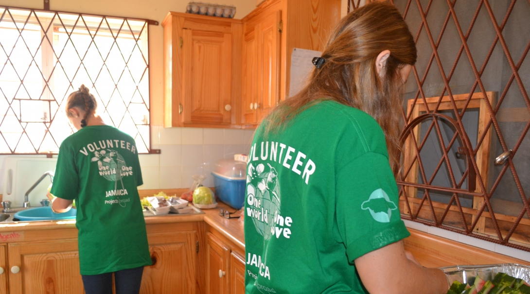 Volunteers working with children in Jamaica with a group help prepare a nutritious breakfast.